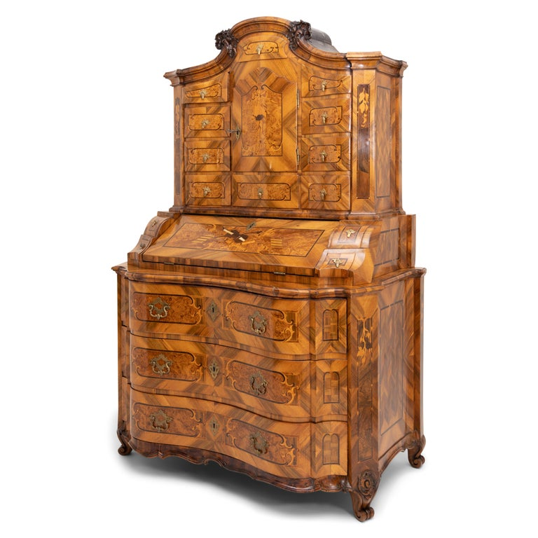 Large Baroque secretaire with a three-drawer chest of drawers in curved form with a wavy skirt. The middle part with a slanted writing flap and four drawers shows a very beautiful marquetry work with violins, flutes and music sheets in different