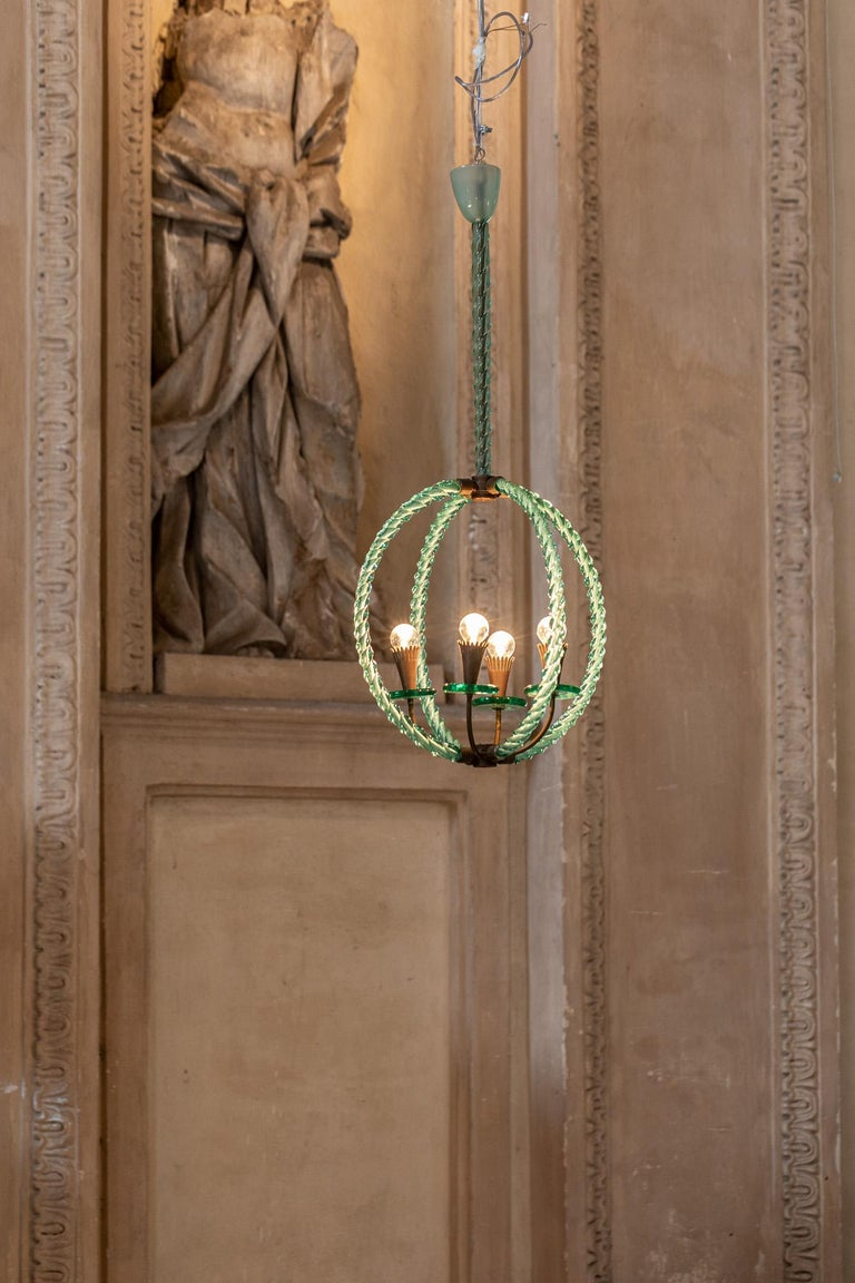 Charming hand blown Murano glass chandelier in the tones of green, with brass details. The structure is composed by two crossing circle elements and four lights.