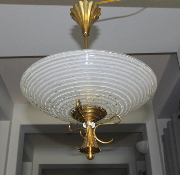 Italian Barovier pendant light with bowl form Murano glass ribbed shade with control bubbles and acid etched back to diffuse light. Glass is suspended on distinctive moderne brass frame and fittings. Fixture uses 2 candelabra base bulbs, newly