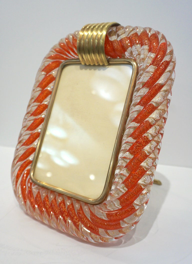 """Mid 20th century modern sophisticated and elegant vintage picture frame in thick blown Murano glass: the crystal clear glass frame worked with """"torchon"""" technique, handcrafted twisted blown Murano glass that amplifies the reflections, is accentuated"""