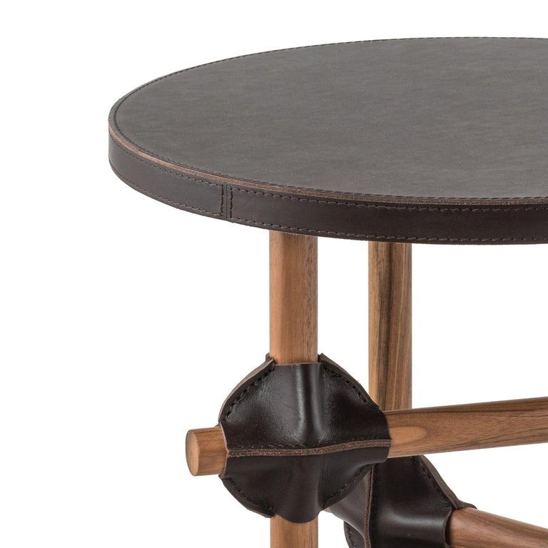 This unique coffee table features a structure in walnut wood, with three legs, connected with horizontal elements and secured with the use of striking leather patches of the same color as the upholstery of the round top. The color, a rich coffee