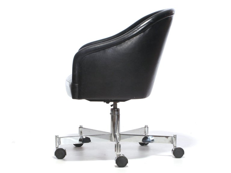 A barrel-back desk chair with the original channel-stitched black leather upholstery, on an X-form caster base. Please inquire for upholstery options.