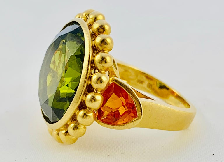 This Ring is an absolute show stopper! Designed by Barry Brinker, it is made in 18K yellow Gold and features a Single, Round, 18mm Peridot that is flanked by two, 7.3mm Orange Sapphires! The retail price on this ring is $7000. It weighs 20.5 grams