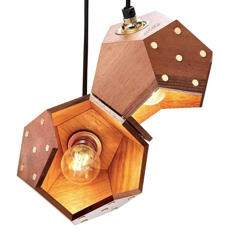 Part of a unique collection of customizable and modular lamps, this is a duo pendant lamp made of two dodecahedrons (15x15x15 cm) crafted of slabs of solid European walnut that were hand assembled. This eye-catching lamp mixes tradition and