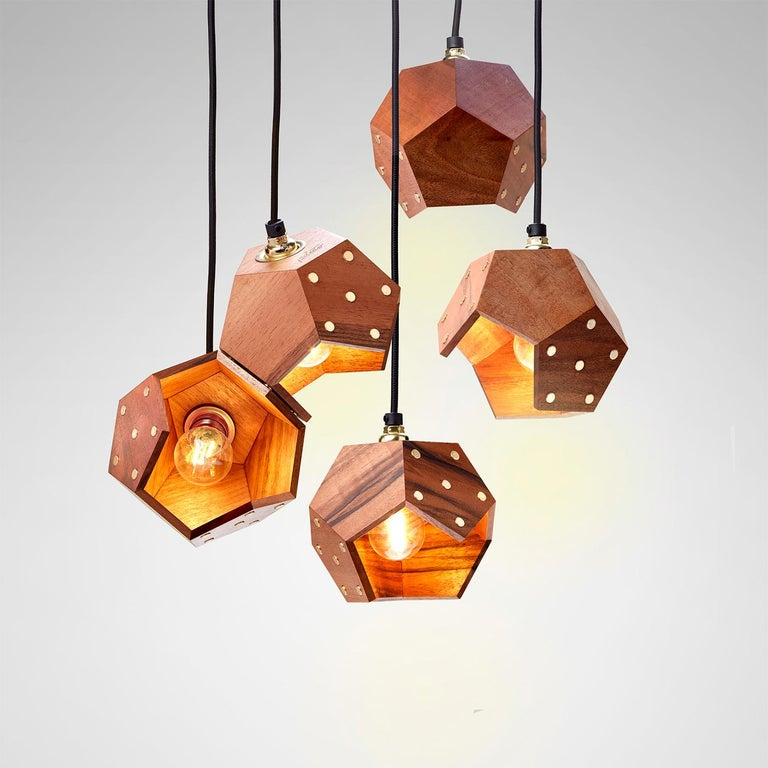 A harmonious combination of tradition craftsmanship and innovative design, this set of five pendant lamps is part of the Basic Twelve collection. Each lamp is a module crafted of thin slabs of solid European walnut hand-assembled in dodecahedrons.