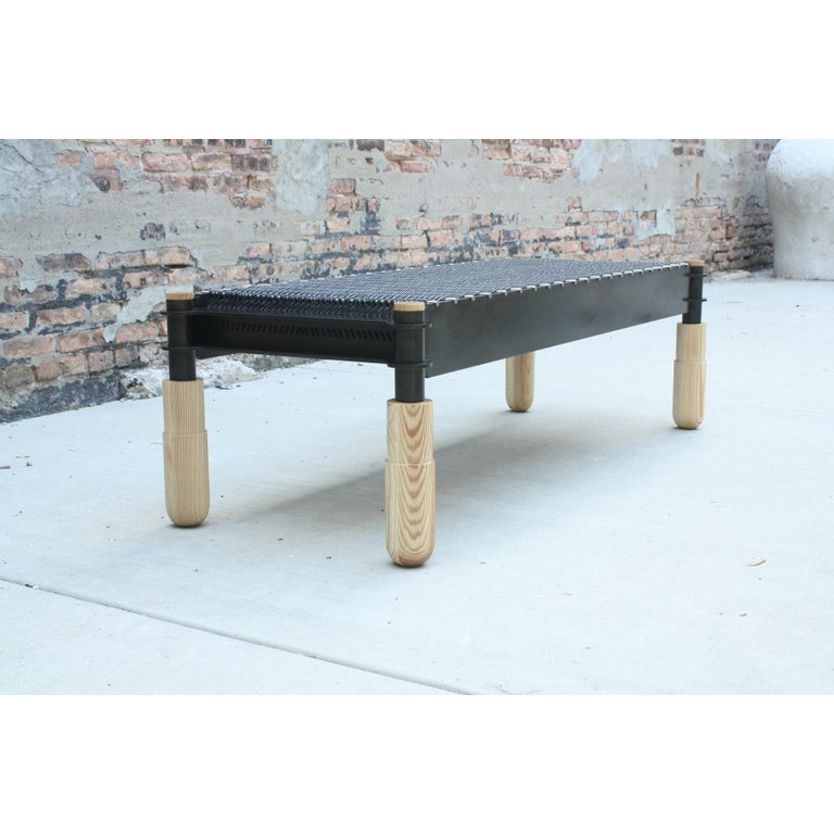 Shown in blackened steel, brushed stainless, oiled ash, and black leather.  This handmade bench features interlocking joinery executed in steel supported by hand-turned solid wood legs. Leather cord is woven through brushed stainless dowels and
