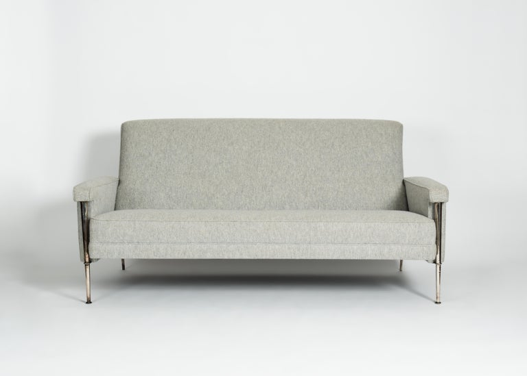 This scaled down midcentury three-seat sofa by Batistin Spade possesses the designer's recognizable thin legs, in this case silvered, and has a broad back set at a charming angle from it's comfortable seat.
