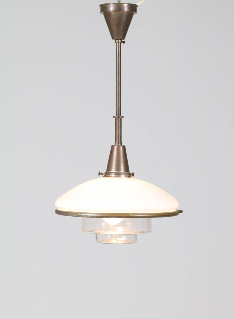 Wonderful Bauhaus pendant lamp. Design by Otto Müller for Sistrah Licht GmbH. Striking German design from the thirties. Brass pendant with two original glass shades. In good original condition with minor wear consistent with age and