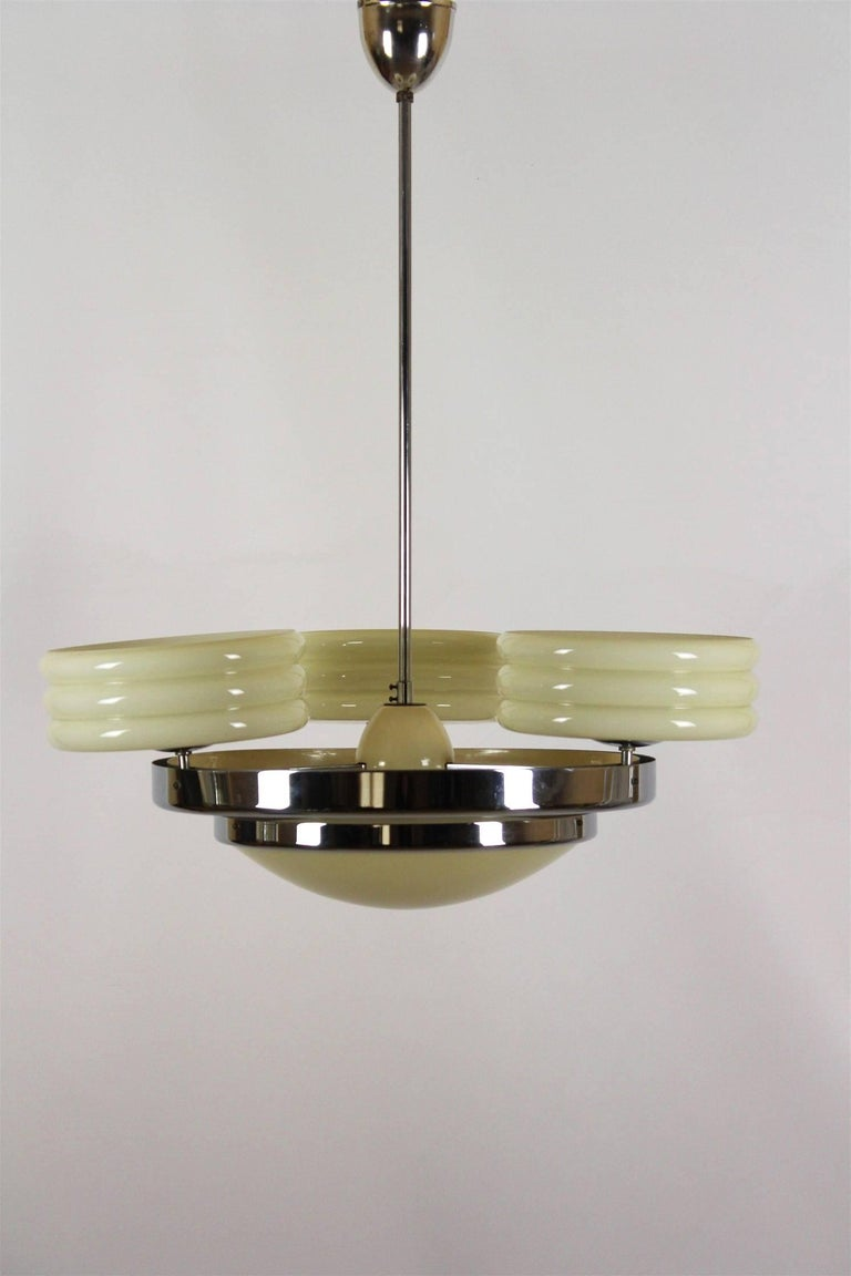 This Art Deco chandelier was manufactured by Zukov in the 1930s. The light is made of chrome-plated steel and opaline glass and is in original condition.