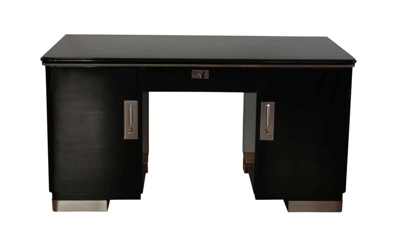 Wonderful spartan Bauhaus Desk from Germany, circa 1930.  Black Piano lacquer on german oak solid wood. Chromed trims on the legs and plate, as well as chromed fittings and keys.  Two doors on the sides and one drawer in the middle. Behind the doors