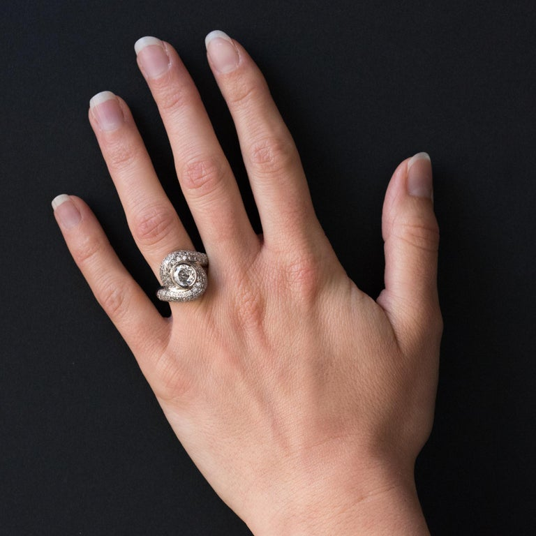 Ring in 18 karat white gold, eagle head hallmark.  This dazzling diamond ring incorporates the lines of the highly popular vortex rings of the 19th Century. With a brilliant cut diamond pave over ¾ of the band, it features a bezel set brilliant cut