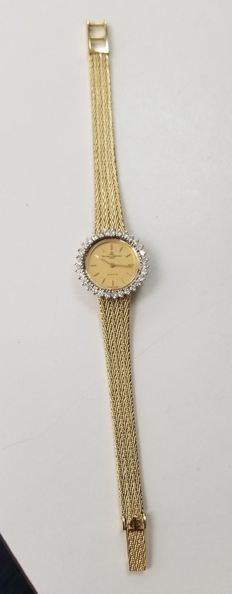 Baume & Mercier 14k yellow gold woven mesh band and diamond watch, containing 31 full cut diamonds of very fine quality weighing 1.00cts.  The watch is in very good condition and measures 6 9/16 or 6 13/16 inches.  the watch has a cabochon sapphire.
