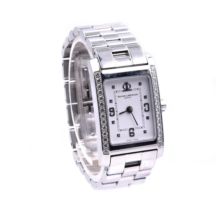 Movement: quartz Function: hours, minutes Case: 26 X 20mm stainless steel rectangular case with diamond sides Band: Baume & Mercier stainless steel bracelet with butterfly clasp Dial: white arabic dial Serial #3787XXX Reference # 65406   No box or