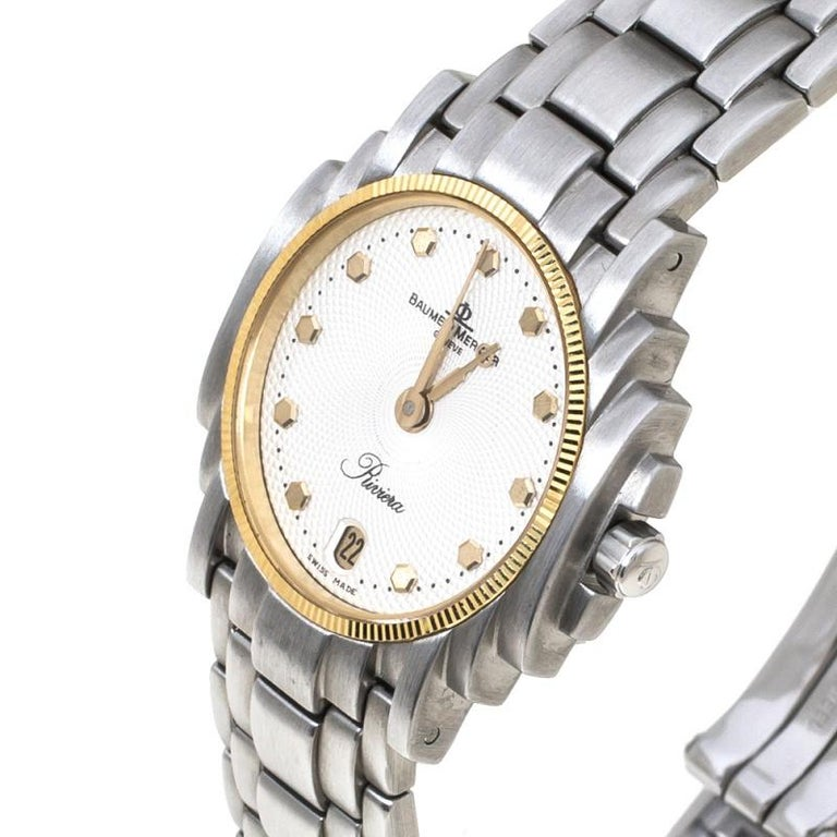 The Baume & Mercier White Stainless Steel Riviera wristwatch exudes style. Made of durable stainless steel, the watch has an elegant dial with gold-tone hour markers and hands The link bracelet is secured by a simple clasp.