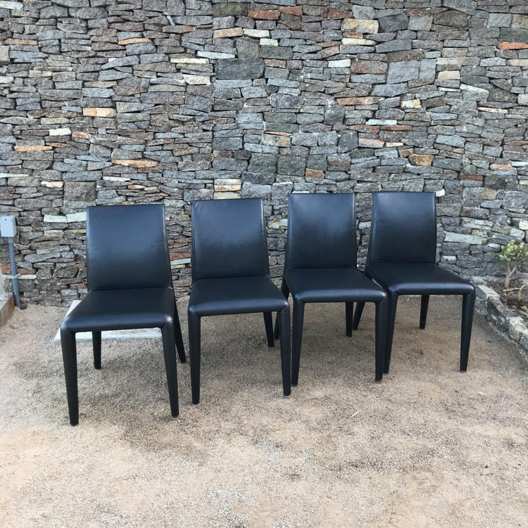 Fabulous Italianset of four dining chairs in sumptuous padded black leather designed by architect Mario Bellini for B&B Italia made in Italy. Solid high quality modern design. Internal tubular steel frame, foam padding, covered in leather. Appears