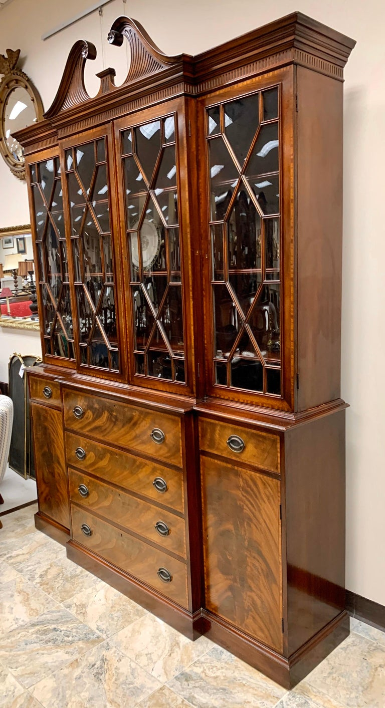 Beacon Hill collection Chippendale style 2 pc china cabinet. This flame mahogany constructed cabinet displays a broken pediment with floret accents, and four glass paneled doors just below opening to three shelves apiece. Each shelf has grooves to