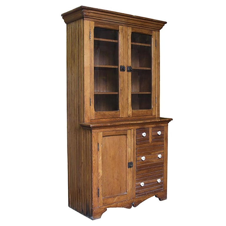 This beautiful beadboard cupboard retains its original iron and porcelain hardware and is just a lovely piece. Fine honey patina, plenty of storage, and original wavy glass, early 20th century, New England.