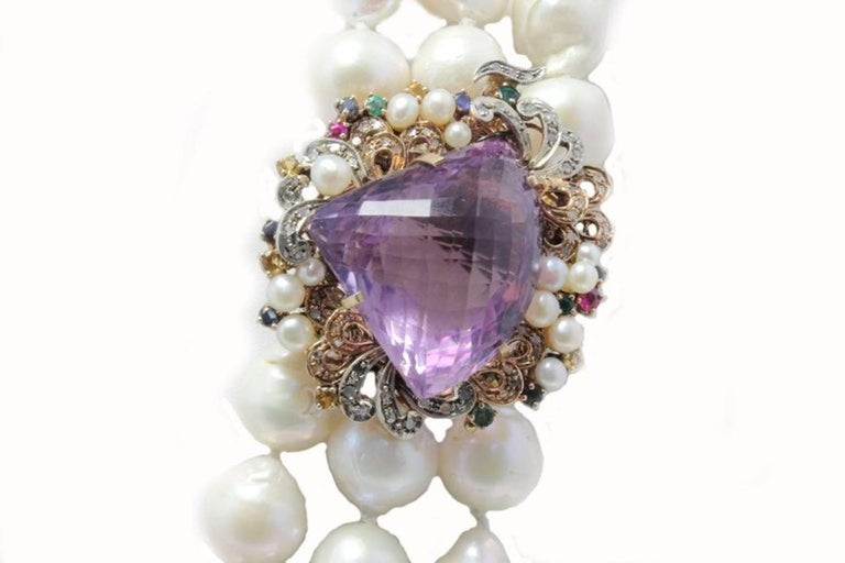 Classic and charming beaded multi strands necklace, embellished with a clasp composed of little pearls, sapphires, emeralds, rubies and diamonds that's surrounding  a shiny amethyst. All is mounted in 9 Kt rose gold and silver. Tot Weight 361.1