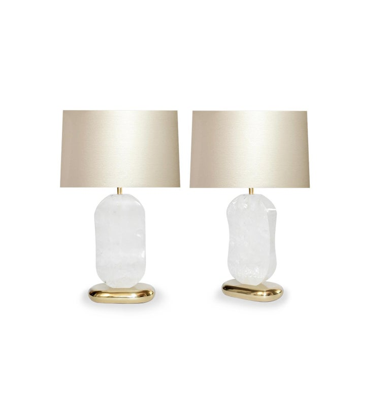 Pair of carved oval form rock crystal quartz lamps with polished brass bases. Created by Phoenix Gallery, NYC. Measure: To the top of rock crystal: 14.35