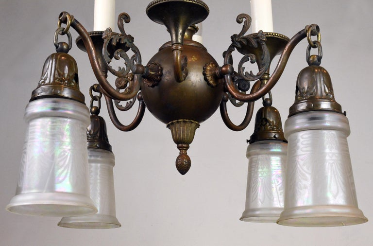 Exquisite brass Beardslee gas/electric chandelier with four candles and four iridescent glass shades. The combination both up and down lighting will provide ample illumination for any number of spaces. The fixture has a beautiful, rich patina: a