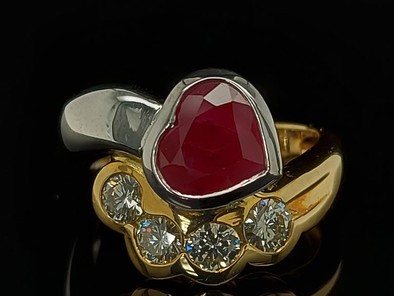 Beautiful 18kt yellow and white gold ring with 4 diamonds and heart shaped ruby  Diamonds: 4 brilliant cut diamonds, together 0.60 cts  Ruby : Heart Shape ca. 2,5 ct  Material: 18kt white and yellow gold  Total weight: 8.4 grams / 0.295 oz / 5.4