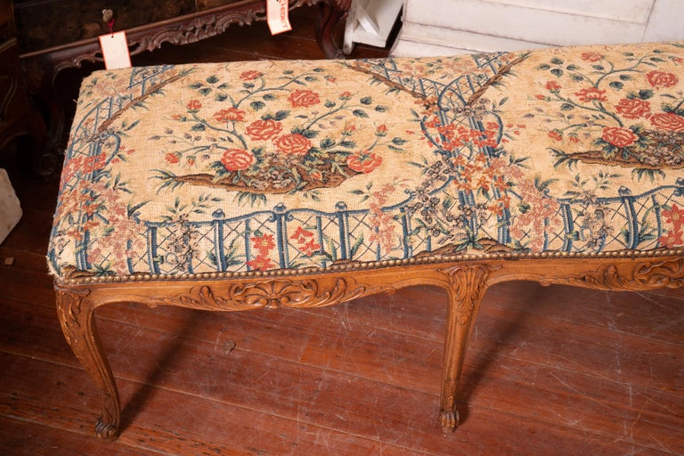 19th century. Carved honey colored walnut bench with original needlepoint cushioning.