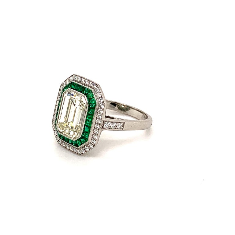 Platinum emerald cut diamond weighing 2.84 carat accented by small round diamonds with the total weight of 0.31 carat and french cut green emeralds weighing 0.50 carat ring