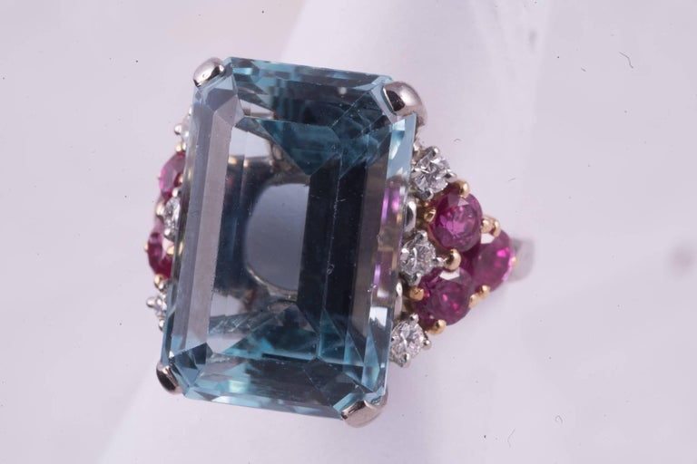 Approx. 13.00cts rectangular cut medium to light blue Aquamarine. There are 6 round cut rubies, 3 on each side of the ring that weigh a total of approx. 1.20cts. There are 3 diamonds on either side of the aqua that weigh approx. .30cts total.