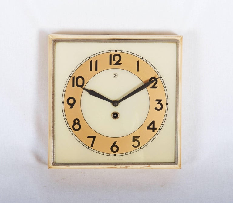Wooden frame with white glass and black digits caught in steel, made by Chomutov/Kienzle in the 1930s. The original movement was changed to an electric one powered by a small battery.