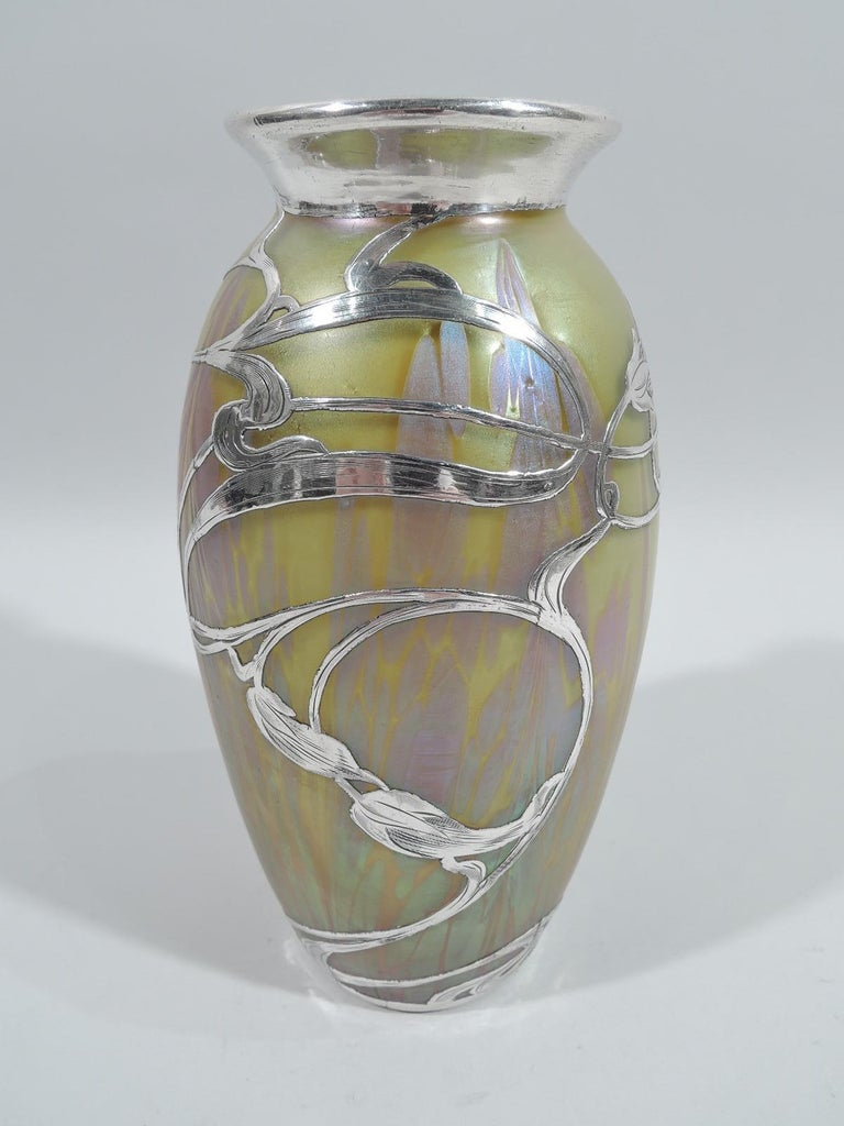 Turn-of-the-century Art Nouveau glass vase by historic Loetz with engraved silver overlay. Ovoid with flared rim. Overlay in form of loose, meandering, and whiplash tendrils with elongated flower heads. Iridescent glass in Medici pattern with