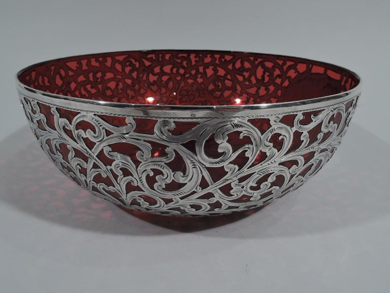 Beautiful Art Nouveau red glass bowl with silver overlay. Made by Alvin in Providence, circa 1900. Round with curved sides and star cut to underside. Engraved overlay in dense scrollwork pattern. Oval cartouche (vacant). Fully marked and numbered