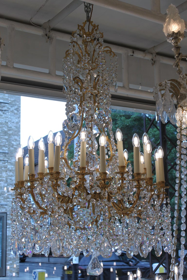 A spectacular and large antique French gilded bronze and cut crystal triple tiers 25-light chandelier embellished with glass cut crystal chains and further adorned with cut crystal prisms by Baccarat. It comes from a famous castle in Burgundy, circa