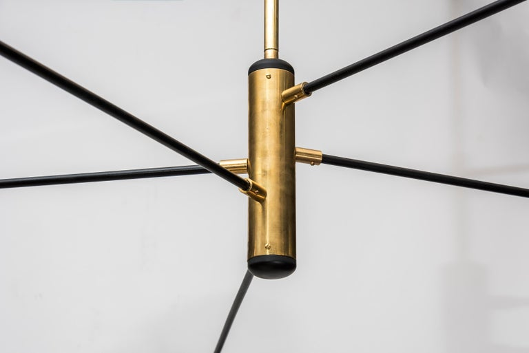 This chandelier designed by Studio Glustin is made of brass. It is composed of five arms holding five lightbulbs under black lacquered lampshades.