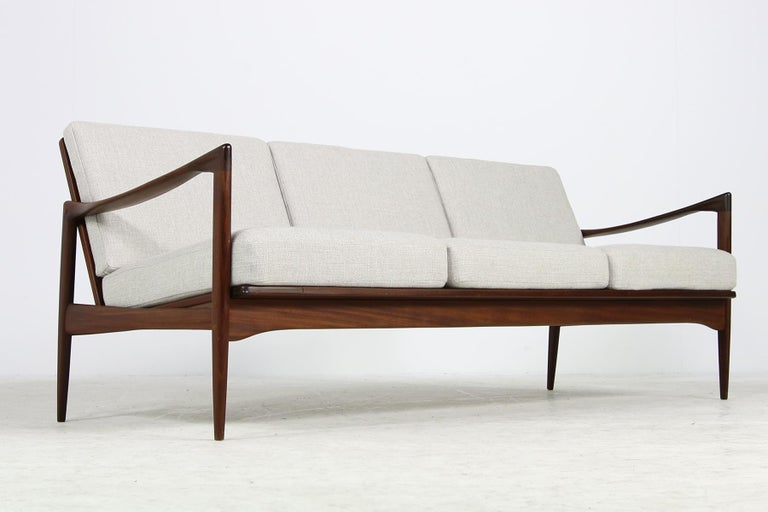 Beautiful, rare 1960s Danish modern teak sofa, designed by Ib Kofod-Larsen, Model 'Kandidaten' in a fantastic authentic condition, the dark, solid teak wood is in a fantastic condition, perfect Minimalist shape, the cushions were upholstered and