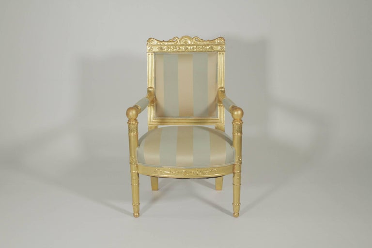 Beautiful gold gilt armchair with silk upholstery, circa 1880-1900. The top rail with dolphin motif corners with open arm sides with cannon ball corners.