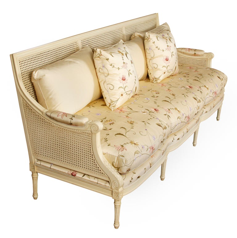Beautiful painted ivory settee with cane back and sides, silk floral fabric seat cushion and pillows and ivory silk back cushions. Carved in Louis XVI style with Vitruvian scroll and floral details on arms and straight legs