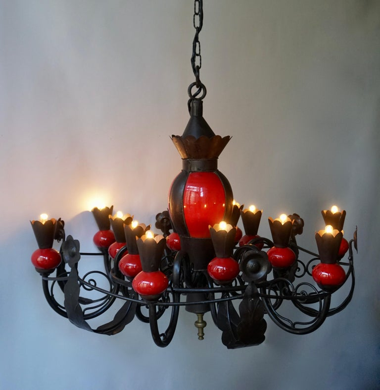A stunning and grand scale French mid-20th century patinated wrought iron and red ceramic 12-light chandelier.  The light requires twelve single E14 screw fit lightbulbs (60Watt max.) LED compatible.  Measures: Diameter 94 cm. Height fixture 74
