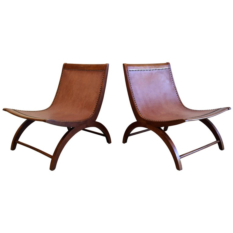 Rare pair of wooden lounge chairs with saddle leather seats.