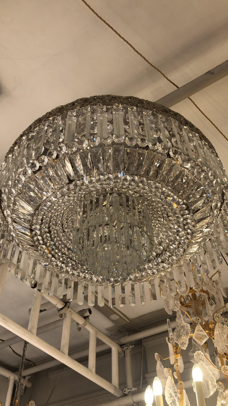 A beautiful pair of Art Nouveau silver crystal circular ceiling mounted chandeliers with graduated acted and cut crystal buttons and prisms. Four tiers starting from an upper decorative filigree gilt brass hoop frame from which Baccarat crystal