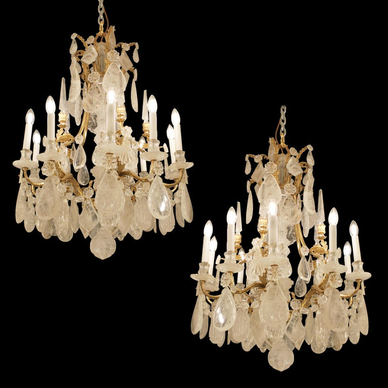 A lovely example of a pair of Baccarat   rock crystals. Features 10-light with 5 rock crystal obelisks with a crown from which rock crystal plaques are suspended. The central stem is surrounded by rock crystal pieces and the surrounding brass frame