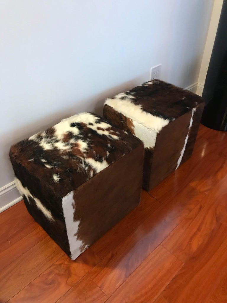 Beautiful pair of modern benches upholstered with cow hide. These ottomans have been re upholstered in cowhide.