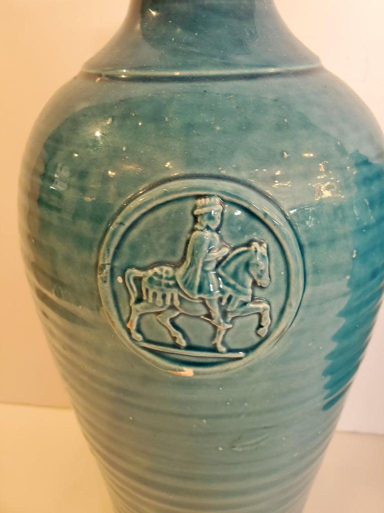 Striking Italian turquoise ceramic vases having relief decorative medallions depicting a knight on horseback.