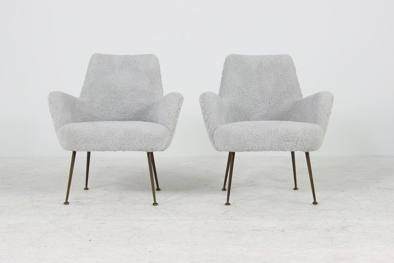 Beautiful and very rare Italian 1950s pair of organic lounge chairs, reupholstered and covered with new super soft teddy fur fabric, solid brass base with nice patina. This pair organic shaped lounge chairs are super rare and very cozy, high