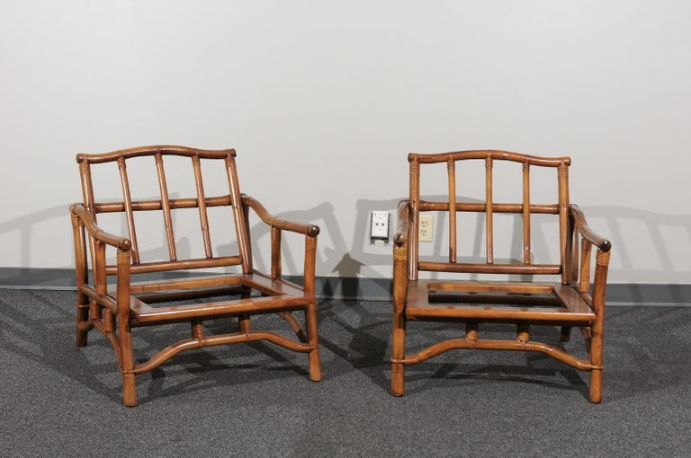 A lovely restored pair of lounge chairs from a low production series by Ficks Reed, circa 1970. Beautifully designed and expertly constructed rattan and hardwood frame with a striking Pagoda detail atop the back. Stout and comfortable. The pieces
