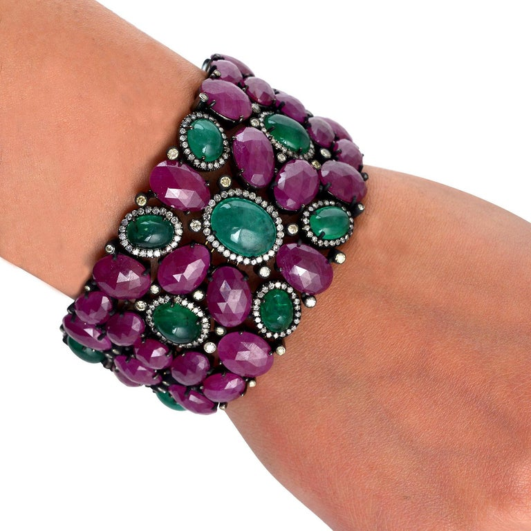 This beautiful Ruby and Emerald Cabochon Bracelet with diamonds sprinkled in between wraps around the wrist perfectly and gives a very dressy look,  Closure: Tongue Clasp  18Kt: 6.591gms Diamond: 3.76Cts Sl: 41.287gms EMERALD: 29.95Cts RUBY: 109.2Cts