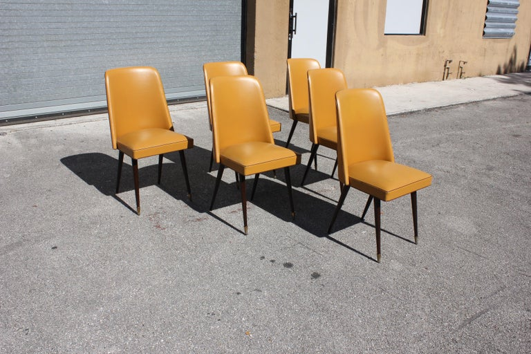 Set of six French Art Deco Gondola dining chairs solid mahogany ,the two front feet are capped with brass ,the chair frames are in excellent condition ,vinyl all around the top . ( Reupholstery is vinyl recommended too be change for all 6 dining