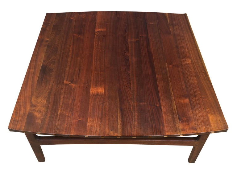 Stunning detailed solid teak Swedish coffee table featuring sculptural lipped edge top with two elegantly curved sides. Exposed wood joinery on the curved edges feature distinctive inlays in lighter, contrasting wood. Exceptional vintage condition