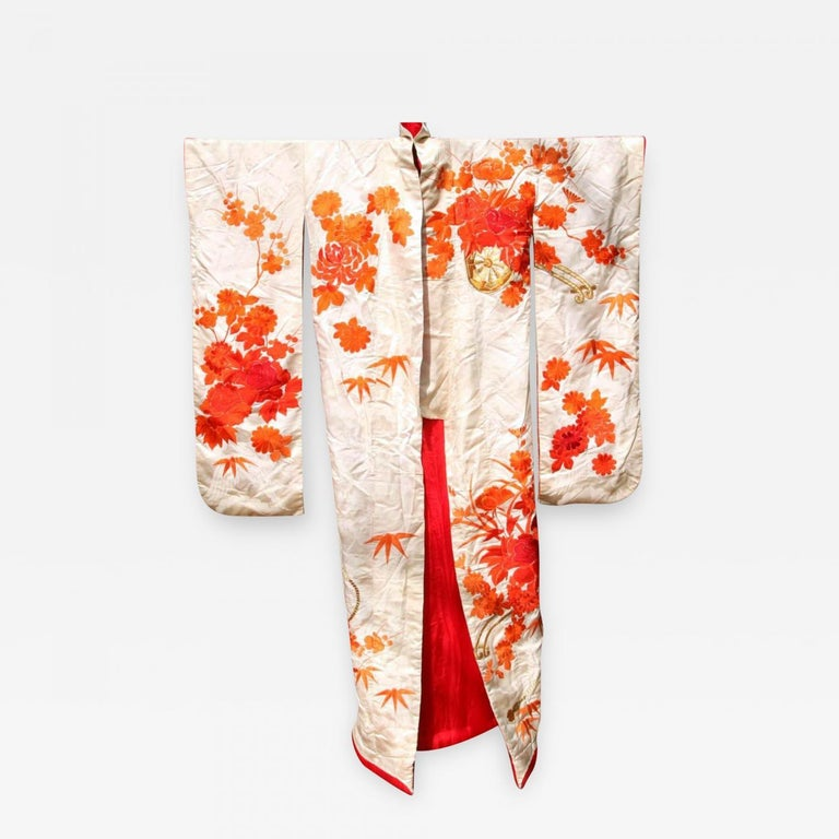 An exceptional Japanese silk wedding ceremonial kimono Uchikake, circa 1930s in the oriental Art Deco fashion. Cream white subtly patterned silk background with elaborate and intricate embroidery in orange, red and gold threads that depict
