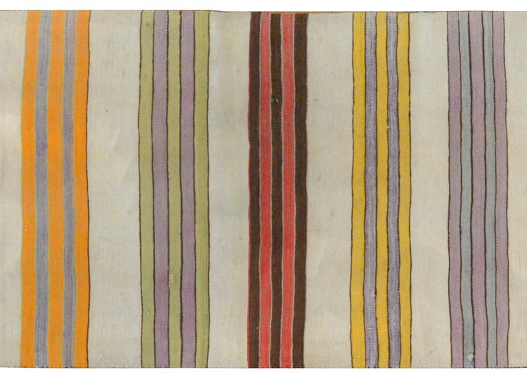 A beautiful vintage mid-20th century Turkish Konya Kilim runner with a striped pattern of pastel colored stripes with a geometric design on each end.