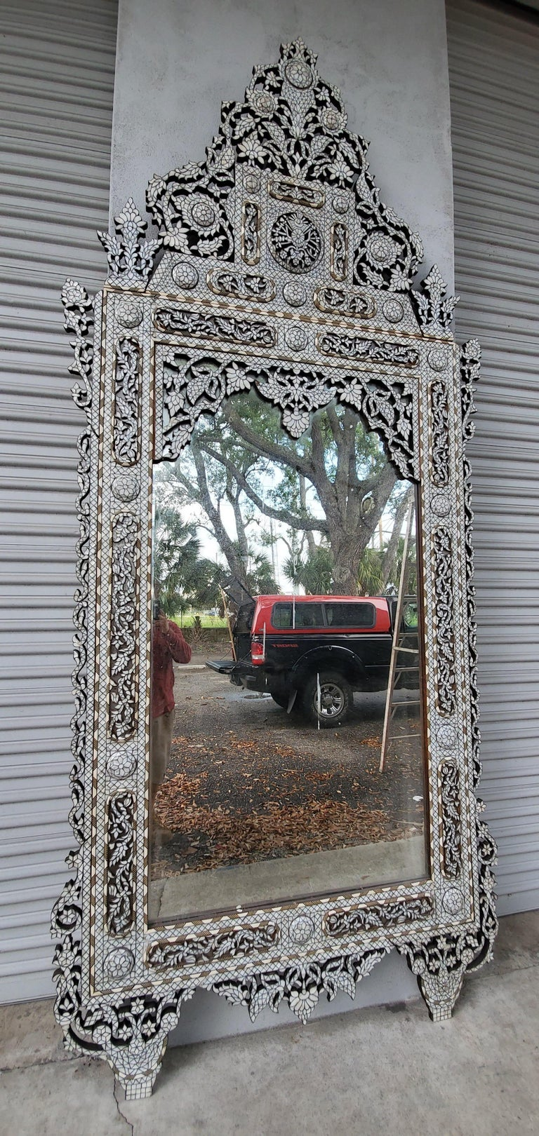 This antique handcrafted inlaid mirror is crafted from individuality cut pieces of mother of pearl and camel bone. The high bonnet top is geometric style design is detachable for easy transport. Details.